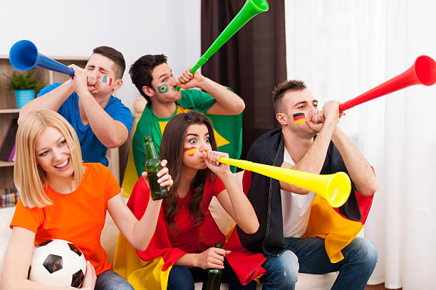 Multinational friends blowing by vuvuzela during the football match stock photo