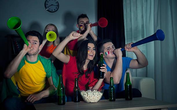 multinational friends cheering football match at home - football friends tv night stockfoto's en -beelden