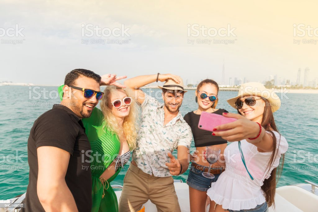Multinational friends having a boat party in Dubai stock photo