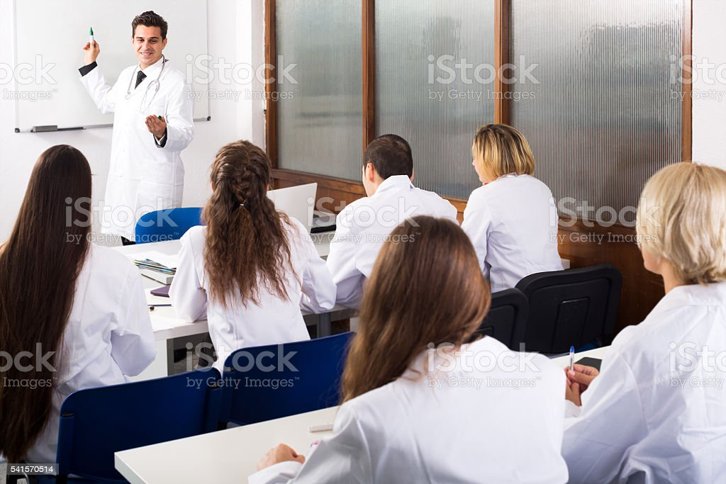 Multinational interns and professor having discussion stock photo