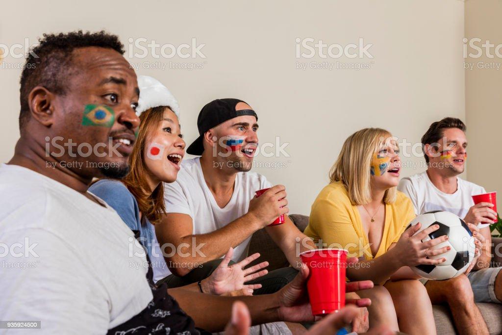 Multinacional de esportes fãs assistindo futebol na TV com alegria e emoção - foto de acervo