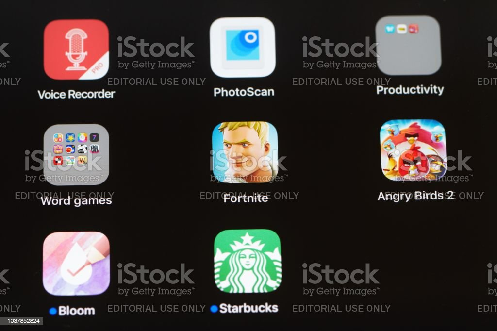 Multiple apps on an iPad screen including video games Fortnite and Angry Bird stock photo