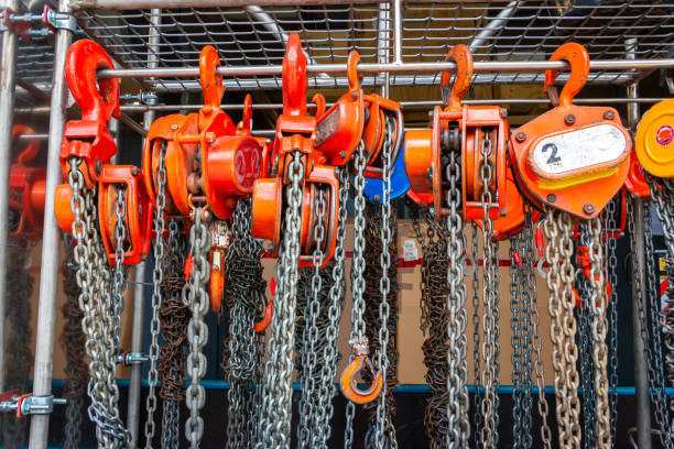 Multiple chain hoists hanging in a rack Multiple chain hoists hanging in a rack ready for use in a industrial environment, picture taken in the Netherlands rigging stock pictures, royalty-free photos & images