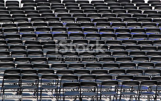 istock Multiple chairs outdoor, many black chair backs 1148825668