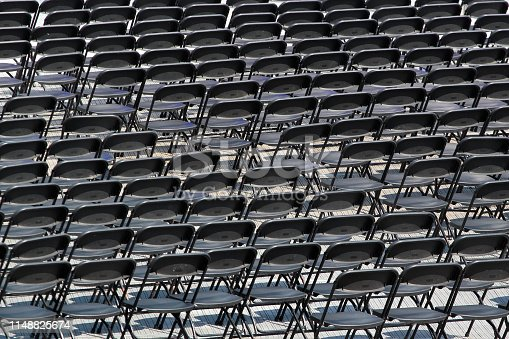 istock Multiple chairs outdoor, many black chair backs 1148825674