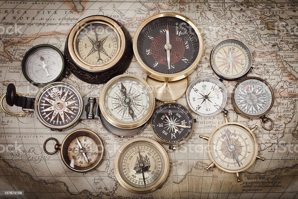 Multiple compasses on an old map stock photo