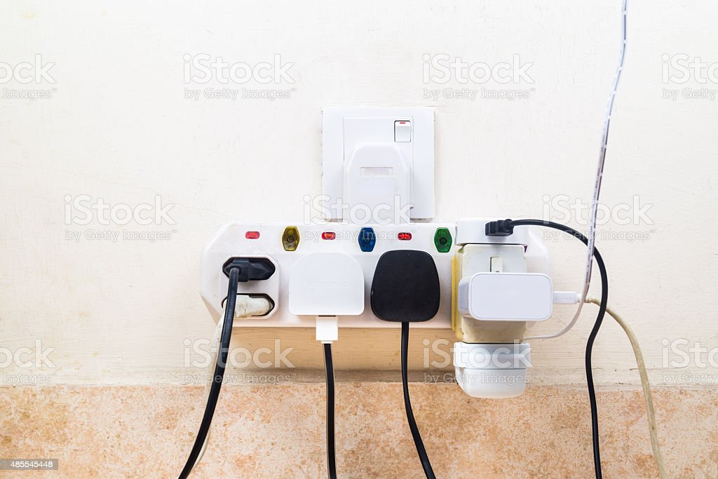 Multiple electricity plugs attached to multi adapter is dangerou stock photo