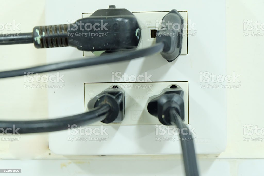 Multiple electricity plugs on adapter risk overloading and dange stock photo