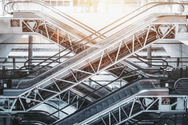 multiple escalators inside of porto airport terminal - escalator foto e immagini stock