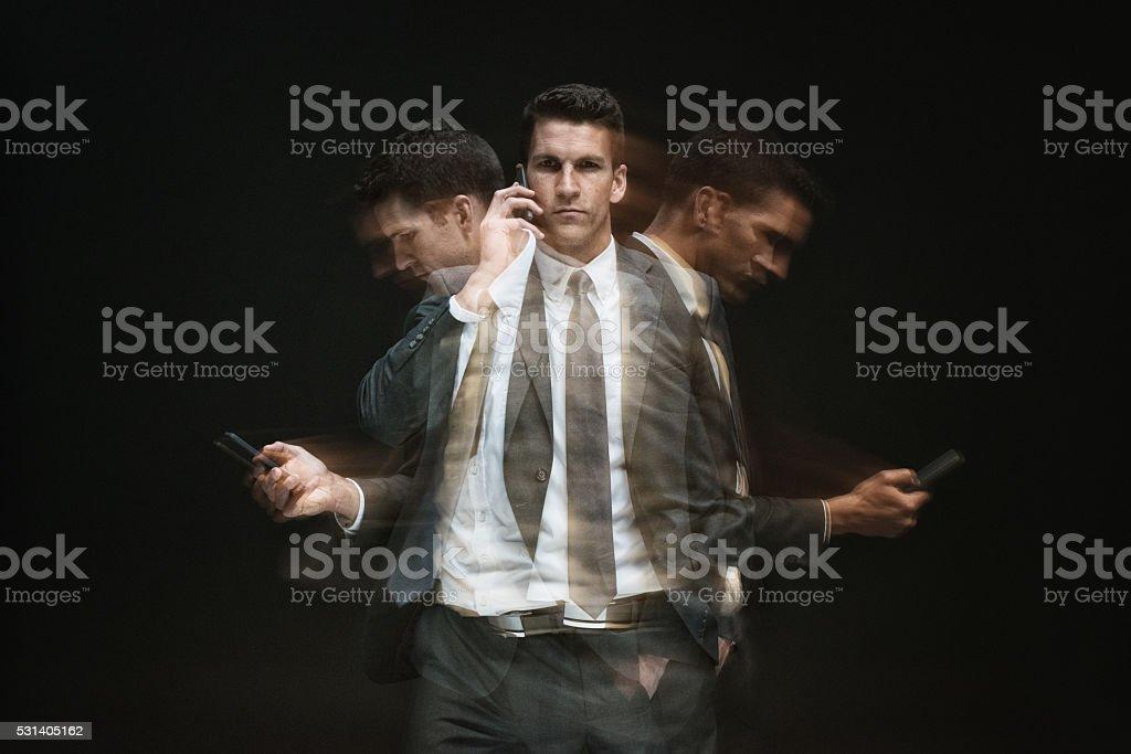 Multiple Exposure - Businessman using phone stock photo