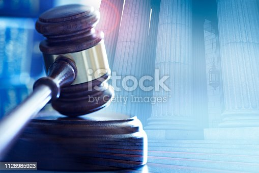A multiple exposure of a wooden gavel and a long row of columns from a courthouse.