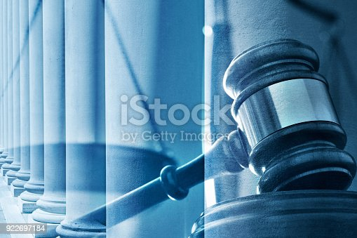 A multiple exposure of a wooden gavel and a long row of Tuscan order columns. A blue color cast dominates the scene.
