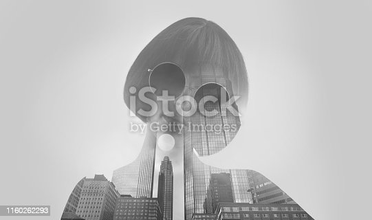 Multiple Exposure of a young woman morphing into cityscape and office buildings