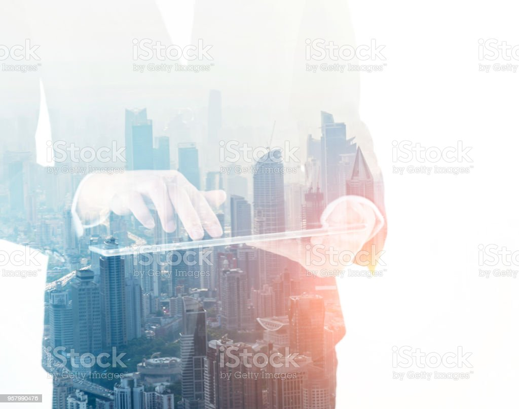 Multiple exposure of businesswoman touching digital tablet stock photo