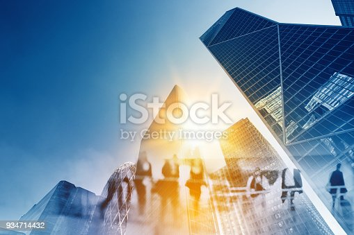 istock Multiple exposure of Silhouettes of people walking in the street near skyscrapers and modern office buildings in Paris business district. Multiple exposure blurred image. Economy, finances, business concept illustration 934714432