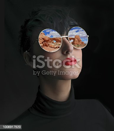 Multiple exposure of woman, sunglasses and Arches National Park rock formation. The Windows.