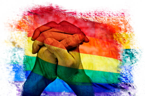multiple exposures of the rainbow flag and the clasped hands of a man stock photo