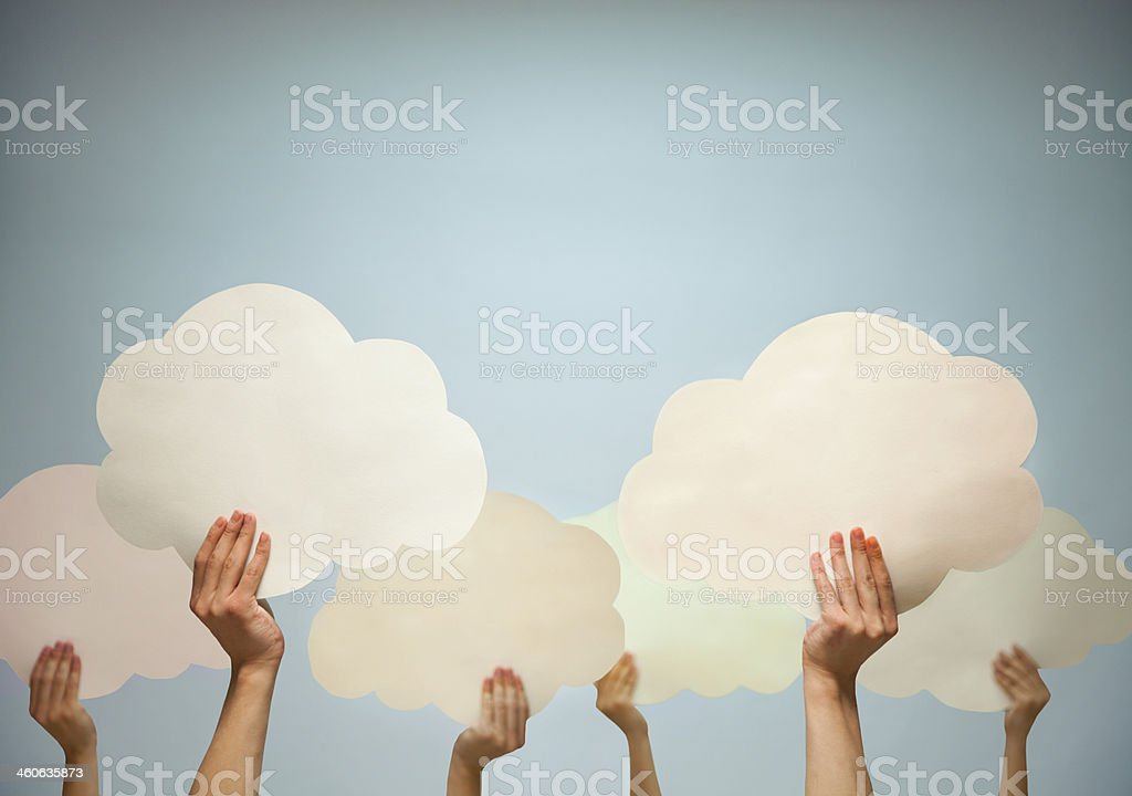 Multiple hands holding cut out paper clouds against blue background stock photo