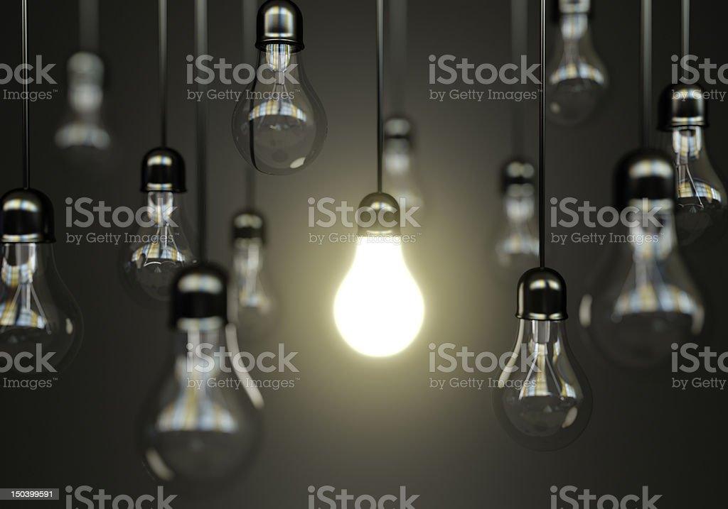 Multiple hanging light bulbs with one illuminated stock photo