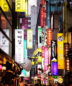 Multiple illuminated commercial signs in Seoul street at dusk. Photographed on Myeongdong street.