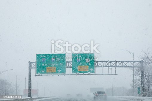 Vehicles traveling along roadway in inclement weather.