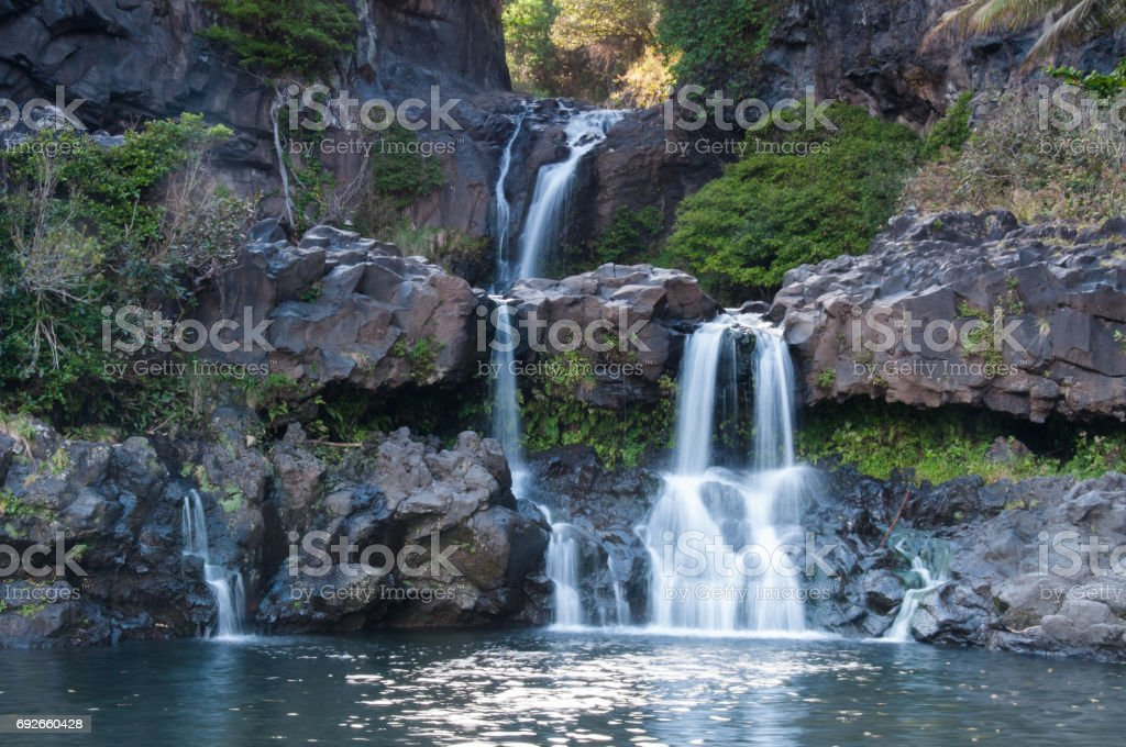 Multiple levels of waterfalls flow into a large pool at the Seven Sacred Pools. stock photo