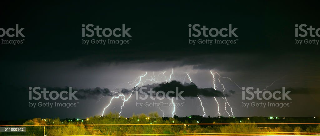 Long exposure capturing multiple lightning flashes with clouds and...