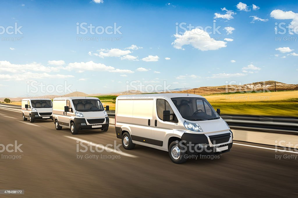 Multiple mini vans in motion on a colorful background stock photo