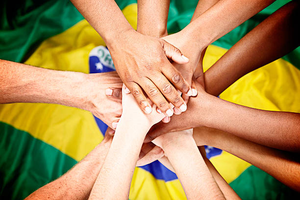 Multiple mixed hands pile onto Brazilian flag pledging loyalty stock photo