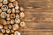 Multiple small scaled raw unwashed edible button mushrooms sitting on top of wooden plank table background