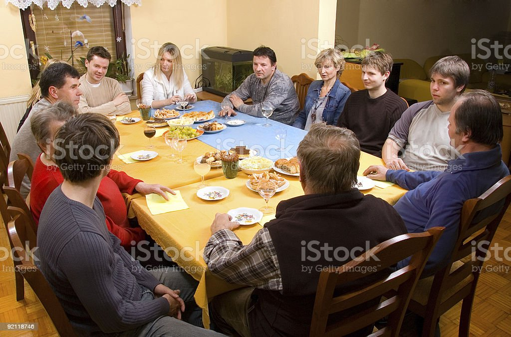 Multiple people sitting around dinner table stock photo