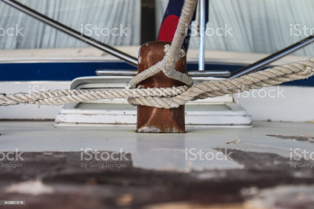 Multiple ropes tied to wooden cleat on vintage wooden boat stock photo