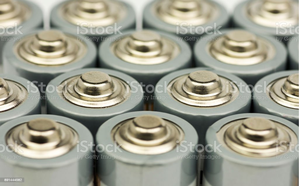 Multiple rows of standing AA batteries with blurred backgrounds stock photo