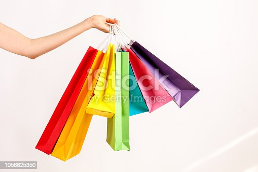 istock Multiple shopping bags of different color in female model's hand. 1056625350