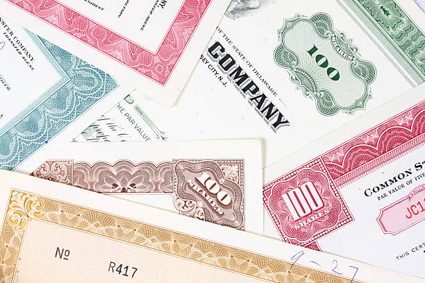 Multiple stock certificates in different colors Corporation investment. Old stock share certificates from 1950s-1970s (United States). Vintage scripophily objects. debenture stock pictures, royalty-free photos & images