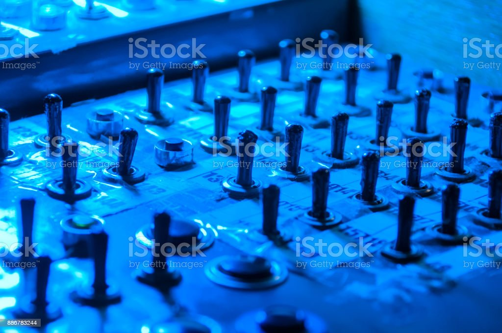 Multiple switches and tumblers in a blue light stock photo