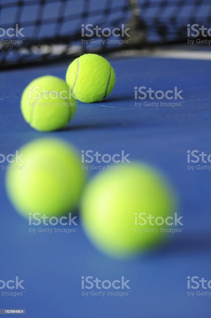 Multiple Tennis balls on the blue court with net stock photo