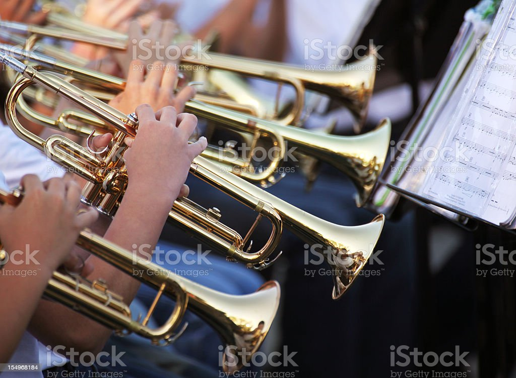 Multiple trumpet players reading sheet music stock photo