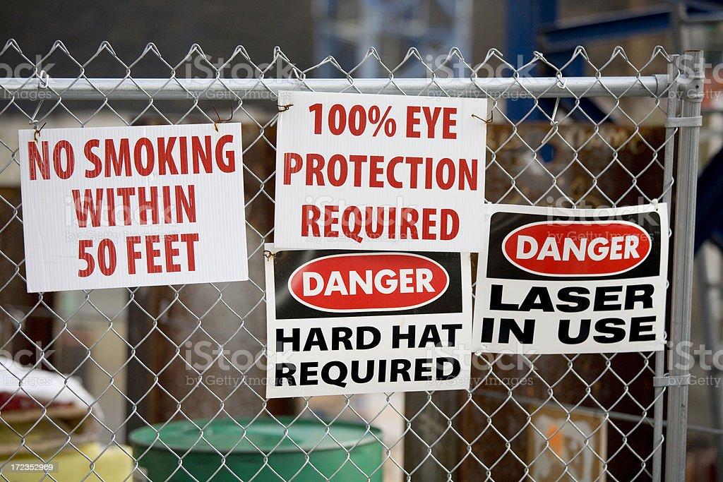 Varias señales de advertencia: Casco duro peligro de láser de protección para No fumadores foto de stock libre de derechos