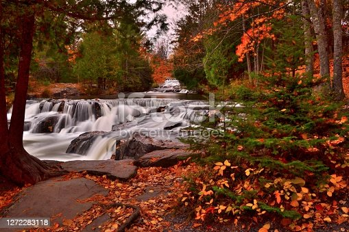 The smaller waterfalls flowing over granite boulders above Bond Falls with the color of autumn. The time exposure evoke feelings of serenity and peace in this autumn forest scenic.  The pathway along the shore is covered with autumn colorful leaves.
