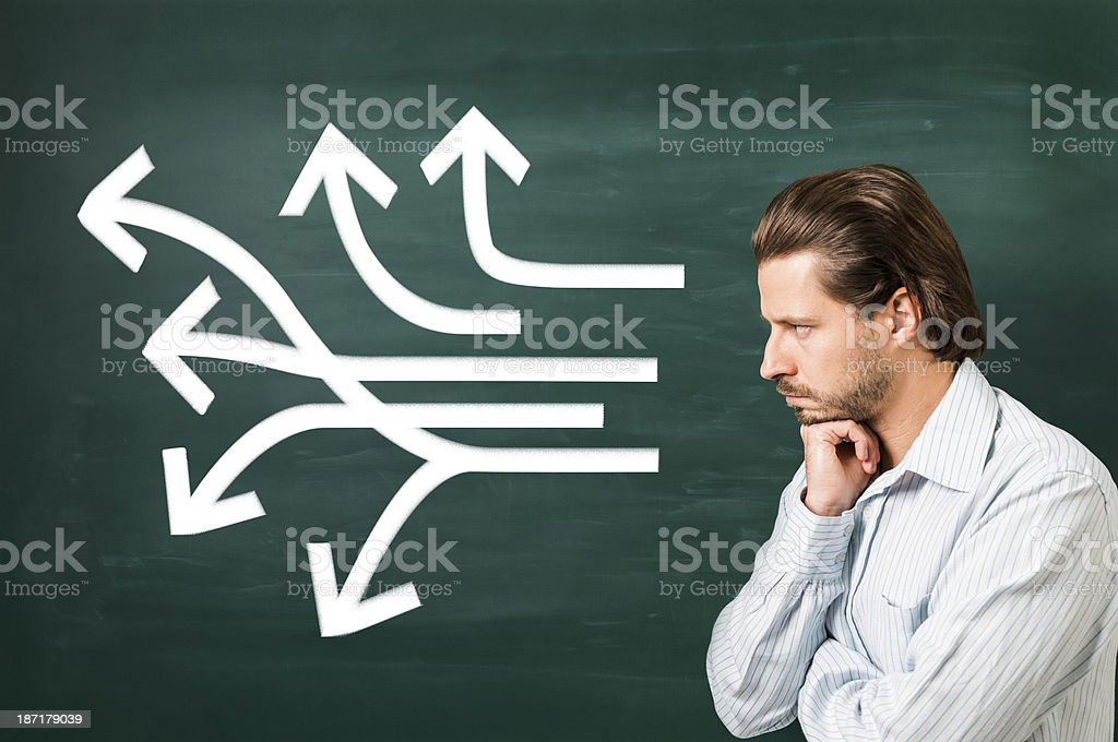Multiple white arrows in different ways on blackboard, thinking man royalty-free stock photo