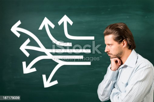istock Multiple white arrows in different ways on blackboard, thinking man 187179039