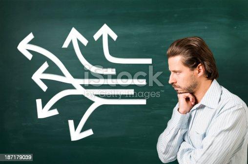 istock Multiple white arrows in different ways on blackboard, thinking man 187179039