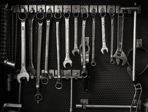 Black and white photo of old multiple wrenches size hanging on tool board in auto car service and maintenance station workshop, Monochrome