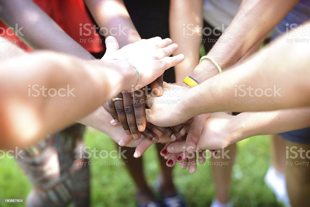 Multiple young adults putting their hands together as a team royalty-free stock photo