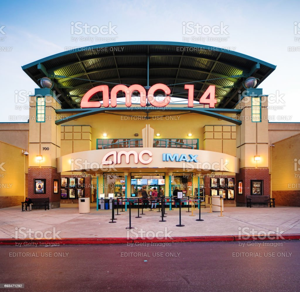 AMC multiplex movie theater entrance facade at sunset with sign stock photo