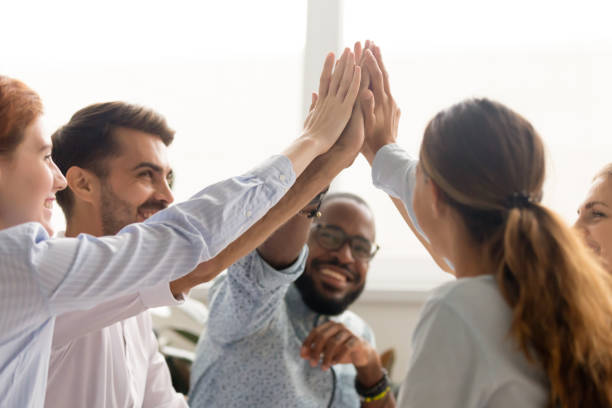 multiracial associate business people group join hands give high five - coinvolgimento dei dipendenti foto e immagini stock