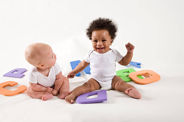 Multiracial babies learning ABC's, playing with letters Multiracial babies learning ABC's, playing with letters having fun babies only stock pictures, royalty-free photos & images