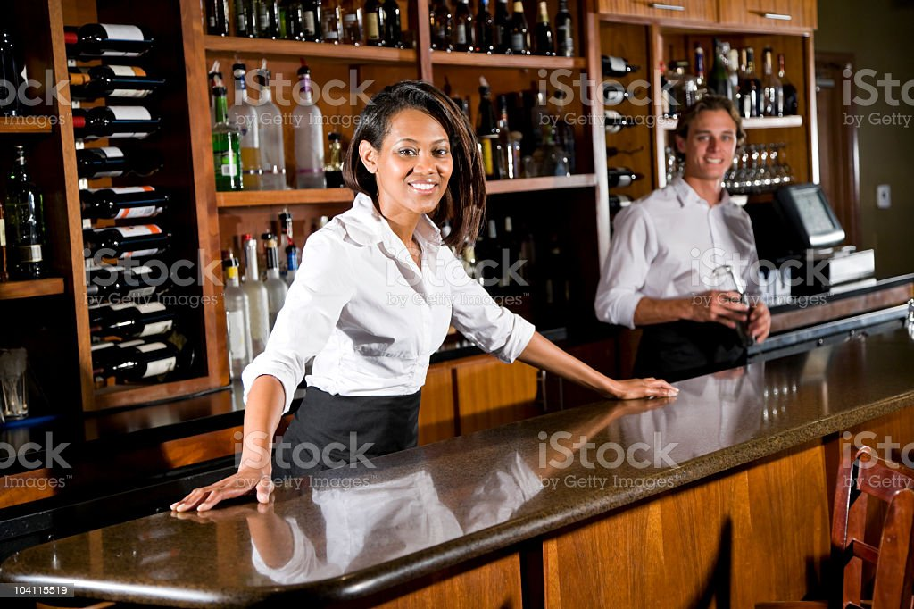 multiracial bartenders working behind bar counter in