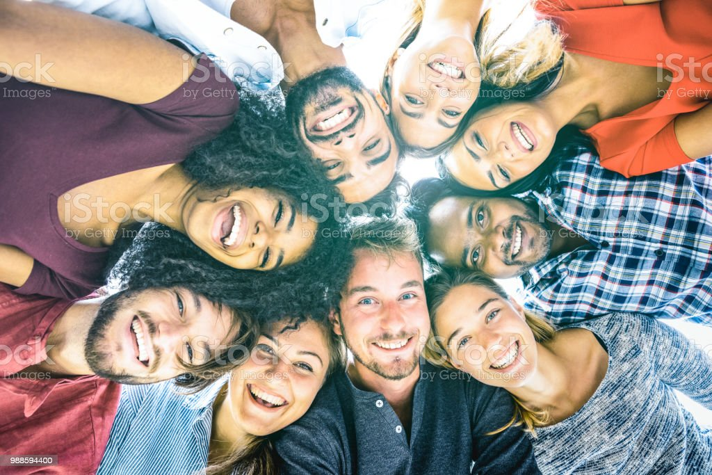 Multiracial best friends millennials taking selfie outdoors with back lighting - Happy youth friendship concept against racism with international young people having fun together - Azure filter tone stock photo